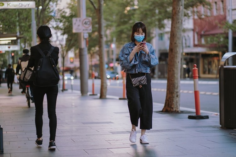 girl using phone while walking on footpath during pandemic